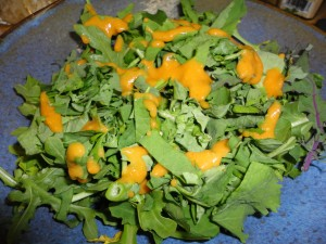 Bottom layer of greens with dressing drizzled over them